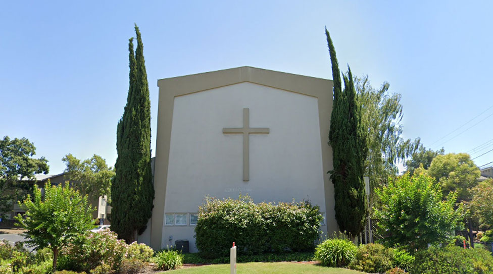 side of the church with a large stone cross
